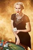 Uma mulher em um vestido preto com os cartões em suas mãos está estando perto da tabela do pôquer Foto de Stock