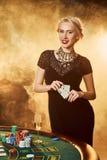 Uma mulher em um vestido preto com os cartões em suas mãos está estando perto da tabela do pôquer Imagens de Stock Royalty Free