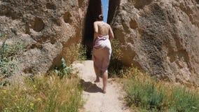 Uma mulher em um vestido vai no verão no trajeto video estoque