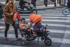 Uma mulher empurra um bebê para andar na estrada fotografia de stock