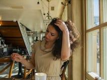 Uma mulher encaracolado-de cabelo senta-se em uma tabela em um café e endireita-se seu cabelo imagens de stock royalty free