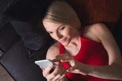 Uma mulher encontra-se no sofá na noite e guarda-se um telefone celular imagens de stock royalty free