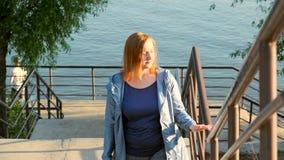 Uma mulher envelhecida média anda acima das escadas do riverbank filme