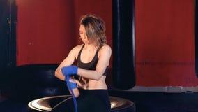 Uma mulher envolve suas mãos com a fita azul do encaixotamento video estoque
