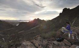 Uma mulher esboça o nascer do sol na montanha de Tetakawi acima de Los Algo fotos de stock