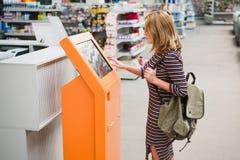 Uma mulher escolhe os bens em linha no dispositivo do autosserviço foto de stock royalty free