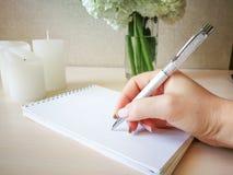 Uma mulher escreve em um caderno com uma pena bonita Imagem de Stock Royalty Free