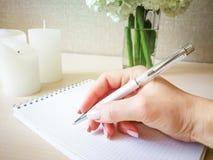Uma mulher escreve em um caderno com uma pena bonita Foto de Stock Royalty Free