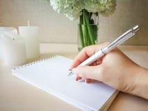 Uma mulher escreve em um caderno com uma pena bonita Imagem de Stock