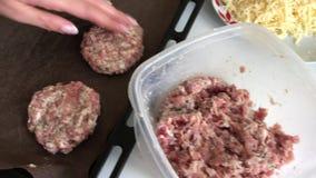 Uma mulher esculpe rissóis triturados da carne e coloca-os em uma folha de cozimento Bifes triturados da carne com batatas, ovos  vídeos de arquivo
