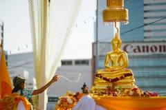 Uma mulher espirra a estátua da Buda com o perfume imagem de stock
