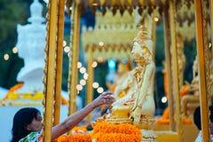 Uma mulher espirra a estátua da Buda com o perfume imagens de stock royalty free
