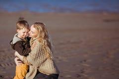 Uma mulher está abraçando seu filho e está tentando-o beijá-lo Imagem de Stock