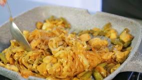 Uma mulher está agitando macarronetes de arroz fritado com galinha e vegetais em uma bandeja video estoque