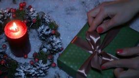 Uma mulher está amarrando uma curva em um presente de Natal vídeos de arquivo