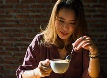 Uma mulher está bebendo o café na casa morna foto de stock