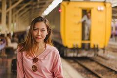 Uma mulher está com um trem na estação fotografia de stock royalty free