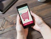 Uma mulher está comprando na loja em linha Ícone do carro de compra Comércio eletrônico Fotografia de Stock