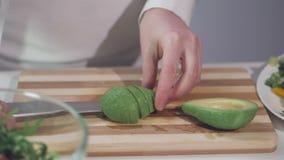 Uma mulher está cortando um abacate maduro com uma faca de cozinha em uma placa de corte video estoque