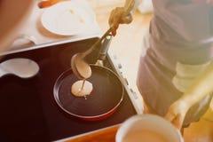 Uma mulher está cozinhando panquecas na cozinha Imagens de Stock Royalty Free
