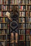 Uma mulher está escolhendo um livro em uma livraria em Ho Chi Minh City, Vietname em fevereiro de 2017 imagens de stock