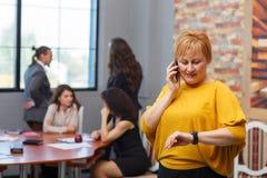 Uma mulher está estando no escritório que olha o pulso de disparo e que fala no telefone No fundo, trabalhadores de escritório imagens de stock royalty free