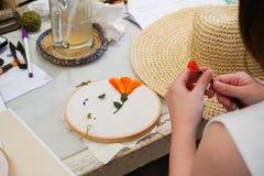 Uma mulher está fazendo o bordado com o outro equipamento do bordado Imagens de Stock Royalty Free