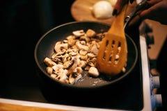 Uma mulher está fritando cogumelos e cenouras O processo de cozimento Fotos de Stock Royalty Free