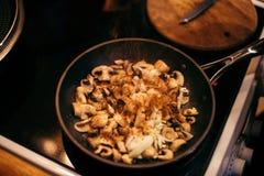 Uma mulher está fritando cogumelos e cenouras O processo de cozimento Imagens de Stock Royalty Free