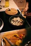 Uma mulher está fritando cogumelos e cenouras O processo de cozimento Imagem de Stock