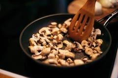 Uma mulher está fritando cogumelos e cenouras O processo de cozimento Fotografia de Stock
