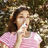 Uma mulher está gotejando gotas nasais em um nariz obstruído Doença e doença Tratamento da sinusite e das alergias Conceito MÉDIC imagens de stock royalty free