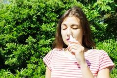 Uma mulher está gotejando gotas nasais em um nariz obstruído Doença e doença Tratamento da sinusite e das alergias Conceito MÉDIC imagens de stock
