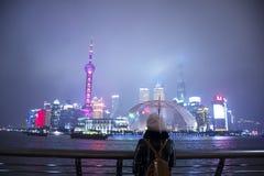 Uma mulher está guardando o guarda-chuva e está olhando a cidade de Shanghai fotografia de stock royalty free