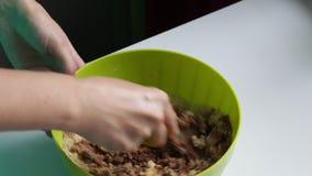 Uma mulher está misturando o cacau, o açúcar, a manteiga, o leite e uma cookie esmagada filme