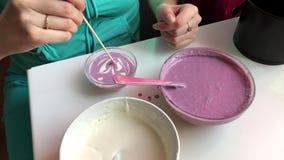 Uma mulher está misturando sua sobremesa de gelatina com uma vara Faz camadas coloridos video estoque