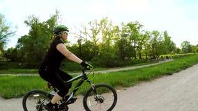 Uma mulher está montando uma bicicleta no parque Movimento lento filme