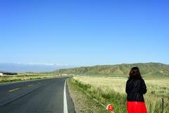 Uma mulher está na estrada na província de Qinghai, China, apreciando a beleza das montanhas neve-tampadas Fotografia de Stock Royalty Free