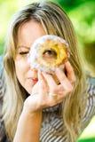 Uma mulher está olhando através do furo no bolo Trdelnik foto de stock