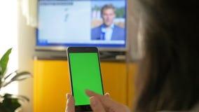 Uma mulher está olhando a tevê, e está guardando um smartphone com uma tela verde No programa televisivo a notícia