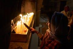 Uma mulher está olhando um grupo iluminado de 33 velas Imagens de Stock