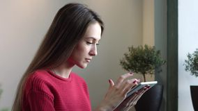 Uma mulher está procurando a informação em um dispositivo vídeos de arquivo