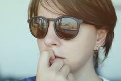 Uma mulher está receosa voar Olha o plano com medo Foco na reflexão dos óculos de sol Fotos de Stock