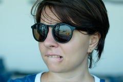 Uma mulher está receosa voar Olha o plano com medo Foco na reflexão dos óculos de sol Foto de Stock Royalty Free