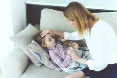 Uma mulher está sentando-se ao lado de uma menina que seja doente Ela ` s que encontra-se no sofá e ela doente do ` s Imagem de Stock Royalty Free