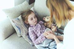 Uma mulher está sentando-se ao lado de uma menina que seja doente Ela ` s que encontra-se no sofá e ela doente do ` s foto de stock royalty free