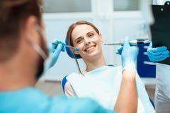 Uma mulher está sentando-se em uma cadeira dental, dentistas dos doutores dobrados sobre ela fotos de stock royalty free