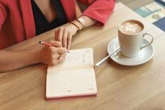 Uma mulher está sentando-se em uma tabela em um café com um livro de reposição Na tabela está uma caneca de cappuccino Conceito d foto de stock royalty free