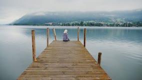 Uma mulher está sentando-se em um cais de madeira Aprecia uma vista bonita do lago da montanha nos cumes, Áustria tiro do steadic filme
