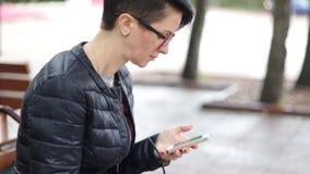 Uma mulher está sentando-se no parque video estoque
